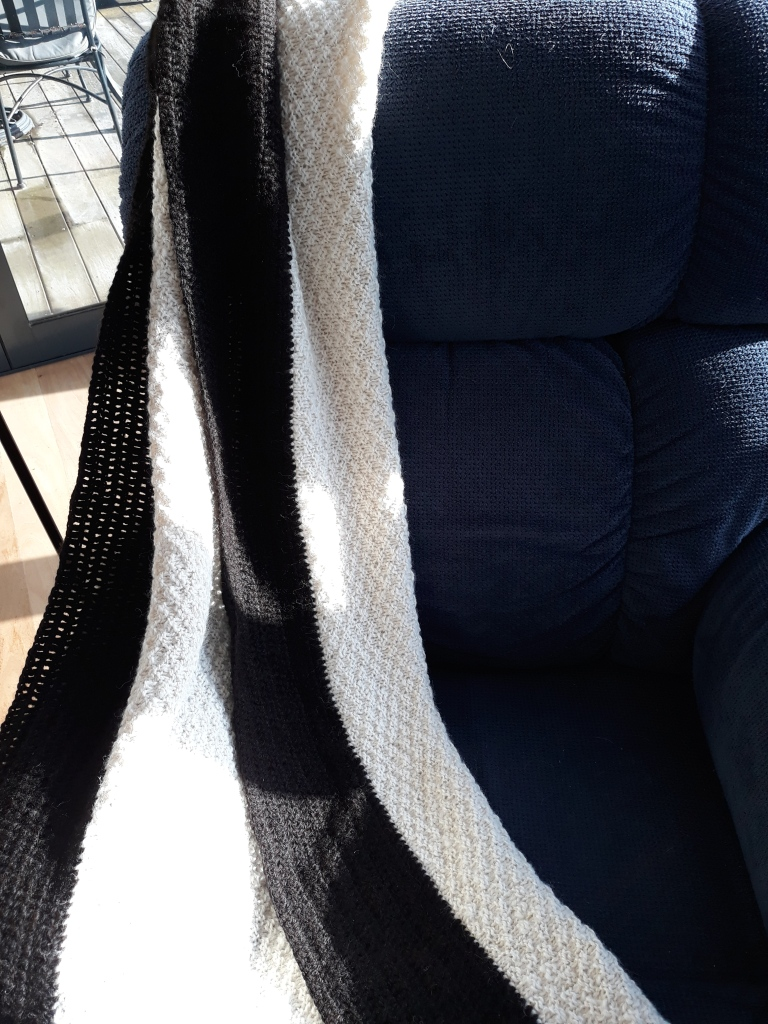 Throw rug/cot blanket, white with black edging $170 NZD